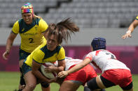 Australia's Evania Pelite looks to pass the baall out under pressure from Japan players, in their women's rugby sevens match at the 2020 Summer Olympics, Thursday, July 29, 2021 in Tokyo, Japan. (AP Photo/Shuji Kajiyama)