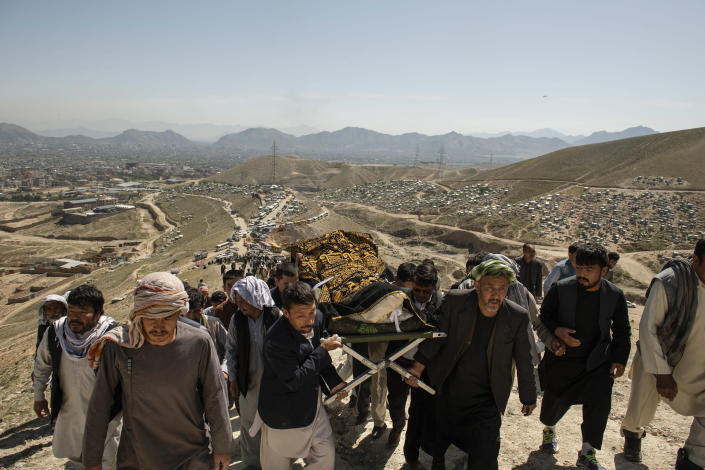 People perform a funeral ceremony on May 9, 2021, for a girl killed in powerful explosions outside a high school in a predominantly Hazara neighborhood in Kabul, Afghanistan. (Kiana Hayeri/The New York Times)