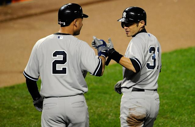 BALTIMORE, MD - OCTOBER 07: (L-R) Derek Jeter #2 and Ichiro Suzuki #31 of the New York Yankees celebrate after they scored on a 2-run double hit by Robinson Cano #24 in the top of the ninth inning against the Baltimore Orioles during Game One of the American League Division Series at Oriole Park at Camden Yards on October 7, 2012 in Baltimore, Maryland. (Photo by Patrick McDermott/Getty Images)