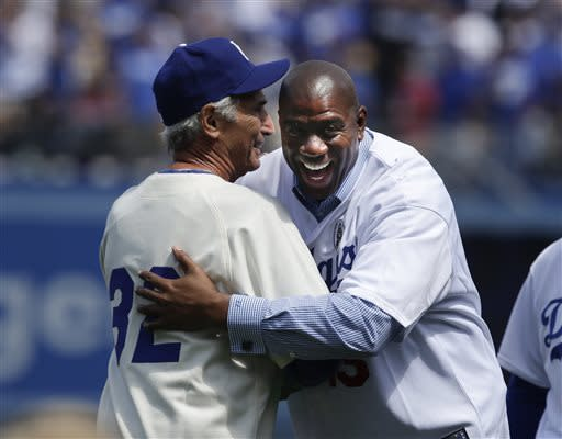 Los Angeles Dodgers owner Magic Johnson, right, hugs former Dodger pitcher Sandy Koufax prior to the Dodger's season-opening baseball game against the San Francisco Giants in Los Angeles, Monday, April 1, 2013. (AP Photo/Jae C. Hong)