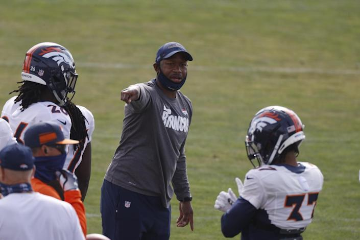 Denver Broncos defensive backs coach Renaldo Hill directs players in drills.