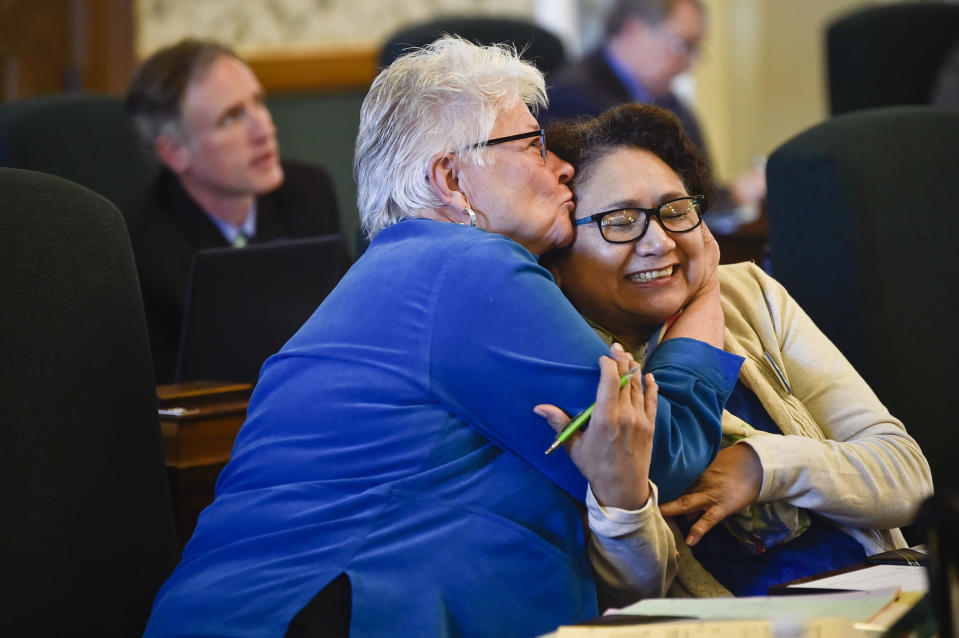 This April 15, 2019 photo, Democratic Sen. Diane Sands of Missoula and Democratic Sen. Susan Webber of Browning celebrate on the Senate floor in Helena, Montana, after the Senate endorsed on second reading a bill to allow the state Department of Justice to assist with the investigation of all missing persons cases. The act was named in memory of woman who was killed on the Northern Cheyenne Reservation in 2013. Webber says the 2021 legislative session is difficult with a bill to end same-day voter registration moving forward along with an attempt to cut funding for two health department positions dedicated to Native American communities. (Thom Bridge/Independent Record via AP)