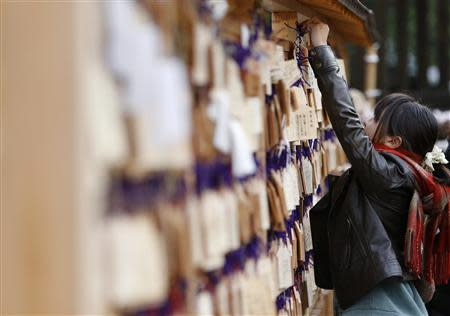 "A girl hooks an ""Ema"" or a small wooden plaque, on which her wishes are written, at the Yasukuni Shrine in Tokyo January 1, 2014. REUTERS/Yuya Shino"