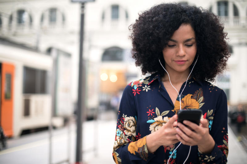 Smiling woman with curly hair using mobile phone at the train station.