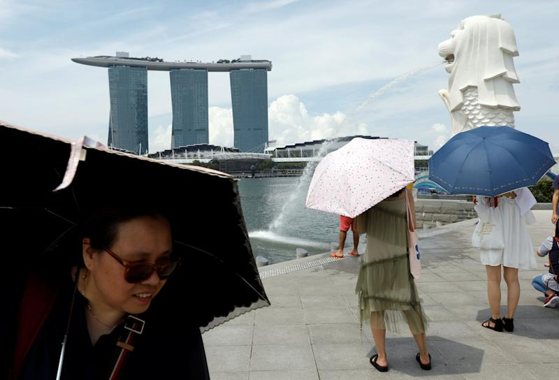 Tourists shield themselves with umbrellas on a hot day at the Merlion Park in Singapore June 21, 2017. REUTERS/Edgar Su