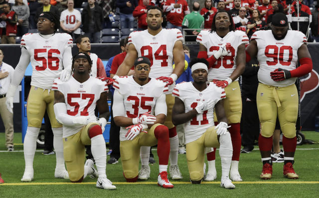 San Francisco 49ers players Eli Harold (57), Eric Reid (35) and Marquise Goodwin (11) kneel during the national anthem before a game against the Houston Texans in Houston on Dec. 10, 2017. (AP/David J. Phillip)