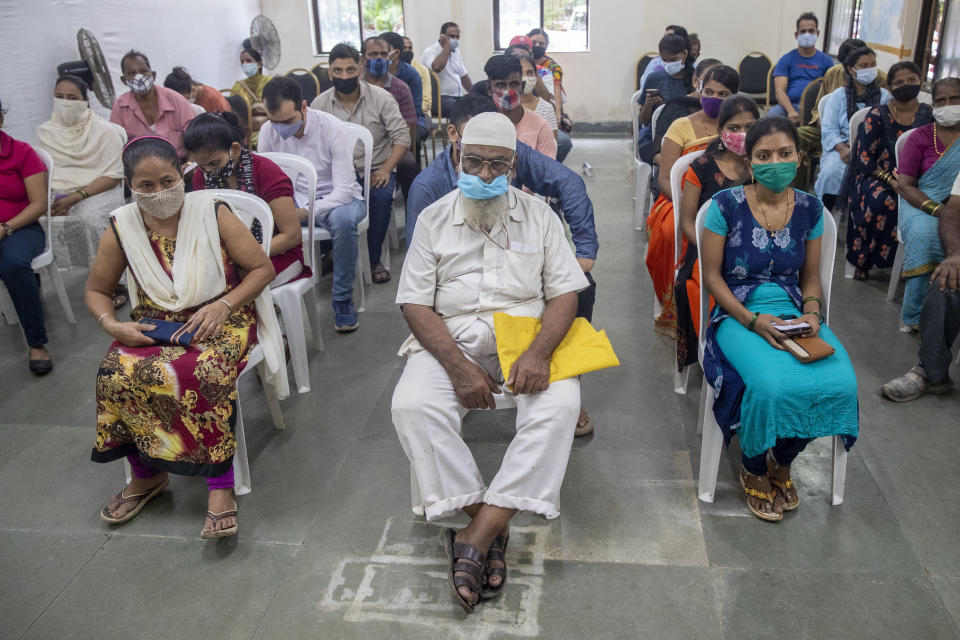 People wait to receive COVID-19 vaccine at a vaccination center in Mumbai, India, Thursday, Sept. 23, 2021. (AP Photo/Rafiq Maqbool)