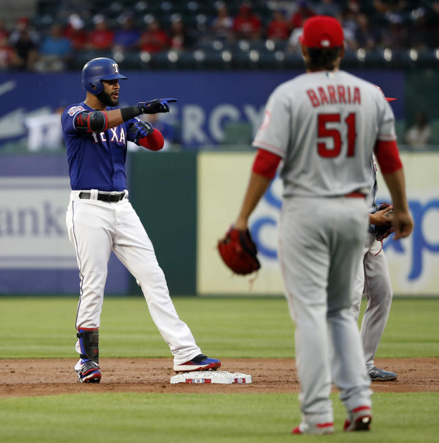 Texas Rangers' Nomar Mazara stands on second pointing at the dugout, celebrating his RBI double, as Los Angeles Angels starting pitcher Jaime Barria (51) watches during the first inning of a baseball game in Arlington, Texas, Tuesday, April 16, 2019. (AP Photo/Tony Gutierrez)