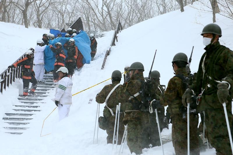 Firefighters carry a survivor from the site of an avalanche in Tochigi prefecture, Japan (AFP Photo/JIJI PRESS)