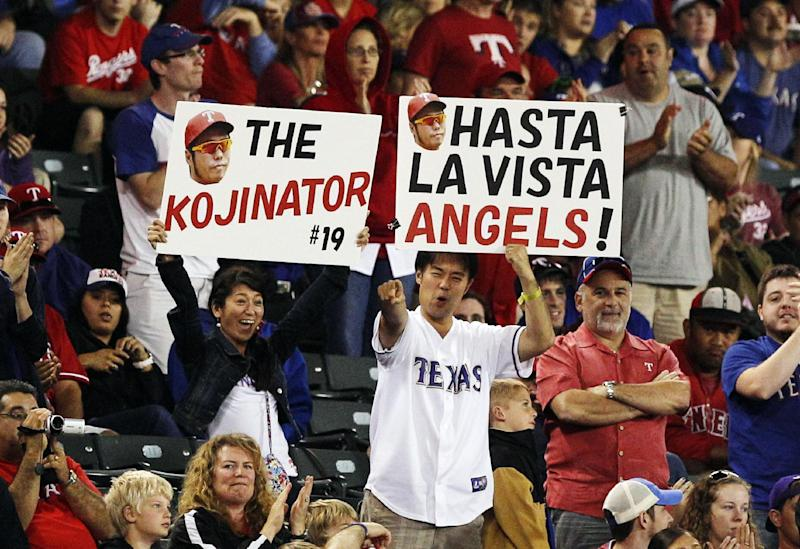 Texas Rangers fans hold signs for relief pitcher Koji Uehara, of Japan, during the second baseball game of a doubleheader against the Los Angeles Angels, Sunday, Sept. 30, 2012, in Arlington, Texas. The Rangers won 8-7. (AP Photo/LM Otero)