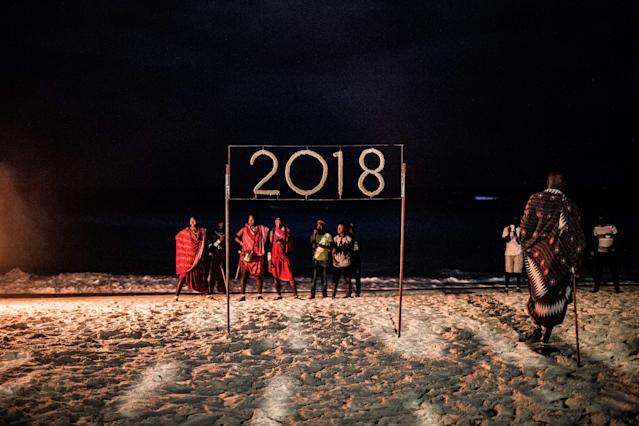 <p>People wait for a moment to light a sign that reads 2018 during the New Year's Eve celebration on Nungwi Beach in Zanzibar, Tanzania, on December 31, 2017. (Photo: Gulshan Khan/AFP/Getty Images) </p>