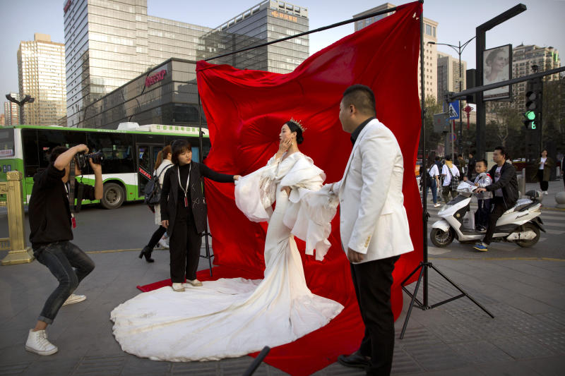"""FILE - In this March 28, 2019, file photo a woman in wedding attire poses for a photo portrait along a busy street in Xi'an in northwestern China's Shaanxi Province. One of the ancient capitals of China, Xi'an is home to the world-renowned Terracotta Warriors. Chinese leaders have long been sensitive about their communist country's international image. Now, they are battling back, investing in diplomacy and a courtship of hearts and minds, just as the United States digs in on the Trump administration's """"America First"""" mindset. (AP Photo/Mark Schiefelbein, File)"""