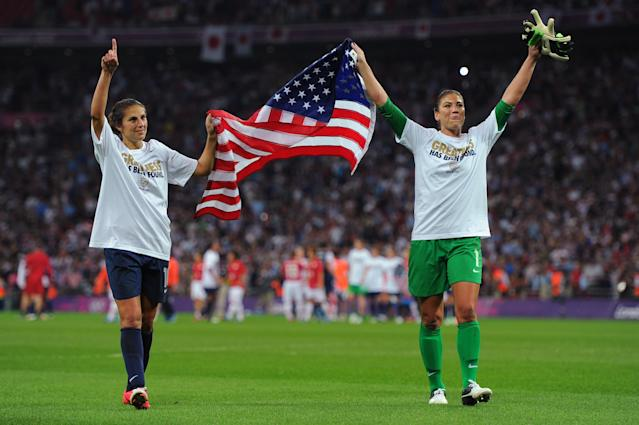 LONDON, ENGLAND - AUGUST 09: Hope Solo #1 and Carli Lloyd #10 of the United States celebrate with the American flag after defeating Japan by a score of 2-1 to win the Women's Football gold medal match on Day 13 of the London 2012 Olympic Games at Wembley Stadium on August 9, 2012 in London, England. (Photo by Michael Regan/Getty Images)