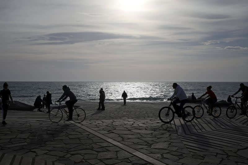 People ride the bikes during an unusual warm, amid the coronavirus disease (COVID-19) pandemic, in the southern suburb of Faliro in Athens