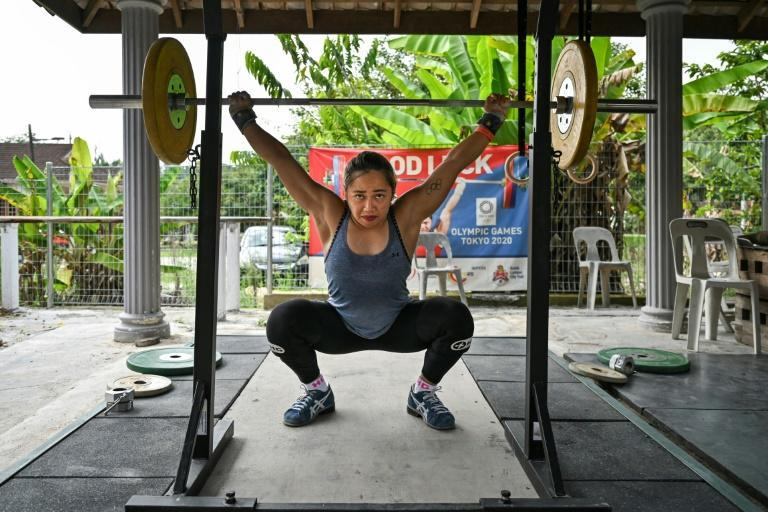 Filipina weightlifter Hidilyn Diaz grunts with the effort of hoisting a barbell over her head in an outdoor makeshift gym ringed by banana and rambutan trees as trucks thunder past -- an unlikely training base for a shot at Olympic gold in Tokyo