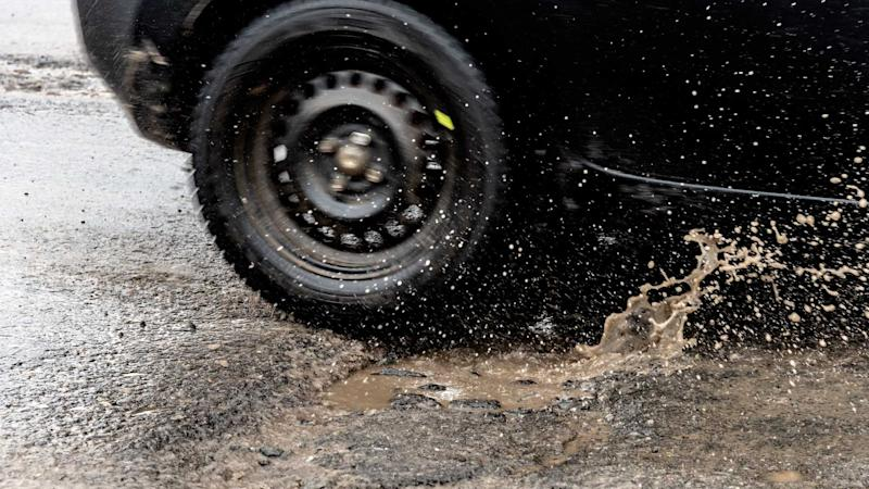 Car driving through a pothole with splashes of water