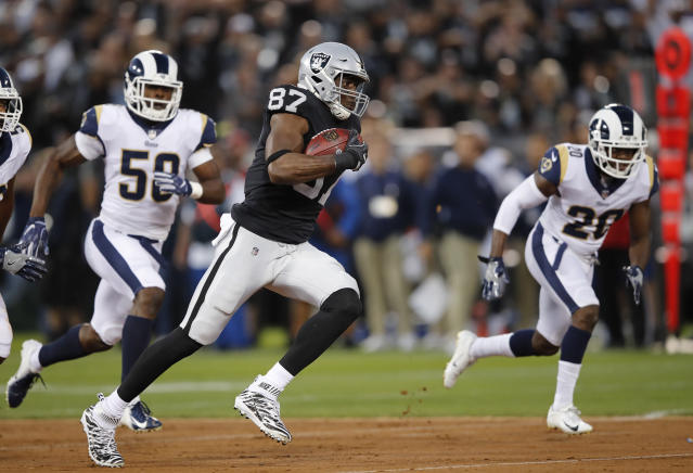 Oakland Raiders tight end Jared Cook runs with the ball past Los Angeles Rams linebacker Samson Ebukam, left, and defensive back Lamarcus Joyner (20) during the first half of an NFL football game in Oakland, Calif., Monday, Sept. 10, 2018. (AP Photo/John Hefti)