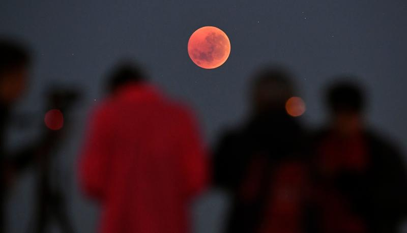 People gather to watch the moon in Melbourne, Australia. (WILLIAM WEST via Getty Images)