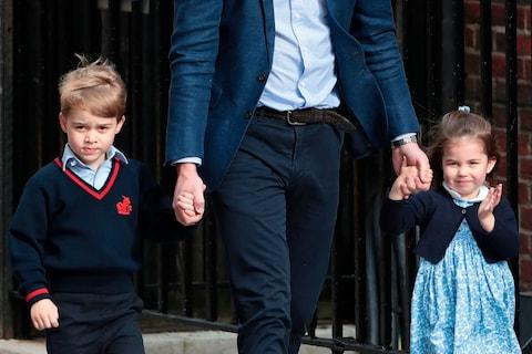 Princess Charlotte of Cambridge (right) waves at the media as she is led in with her brother Prince George of Cambridge (left) by their father Britain's Prince William (centre) at the Lindo Wing of St Mary's Hospital - Credit: Daniel Leal-Olivas/Getty/AFP