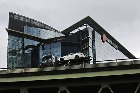 A car transporter drives past the office of pharmaceutical giant GlaxoSmithKline in London