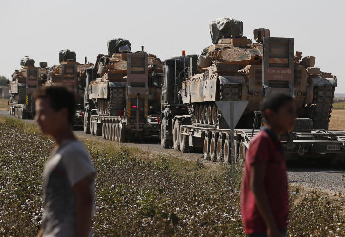 Local residents look on as a convoy of Turkish forces' trucks transporting tanks is driven on a road towards the border with Syria in Sanliurfa province, Saturday, Oct. 12, 2019. Turkey's military said it captured a key Syrian border town under heavy bombardment Saturday as its offensive against Kurdish fighters pressed into its fourth day with little sign of relenting despite mounting international criticism. (AP Photo/Lefteris Pitarakis)