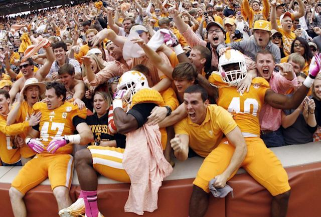 Tennessee linebacker Raiques Crump (40), defensive back Michael F. Williams, center, and linebacker John Propst (47) celebrate with fans after their 23-21 victory over South Carolina in an NCAA college football game on Saturday, Oct. 19, 2013 in Knoxville, Tenn. (AP Photo/Wade Payne)