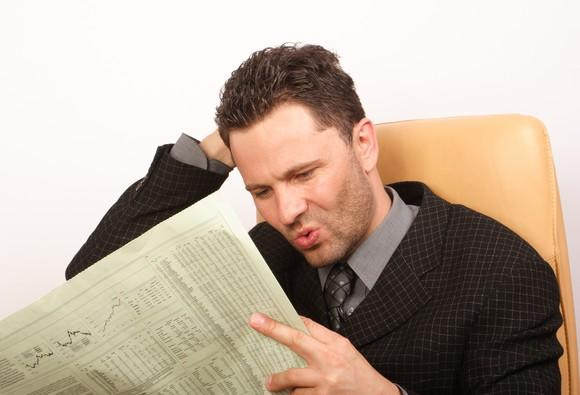 Man wearing suit looking at financial section of newspaper and looking displeased