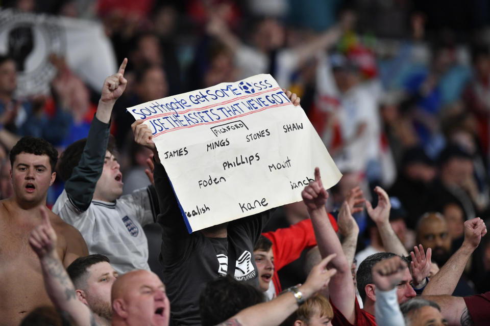An England supporter holds up a poster suggesting his team lineup to England's manager Gareth Southgate during the Euro 2020 soccer championship group D match between the Czech Republic and England at Wembley stadium in London, Tuesday, June 22, 2021. (Justin Tallis, Pool photo via AP)