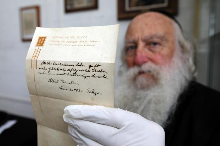 An Ultra-Orthodox Jewish man displays a note written by Albert Einstein in 1922 on hotel stationary from the Imperial Hotel in Tokyo, Japan, at the Winner's auction house in Jerusalem on October 19, 2017 (AFP Photo/Menahem KAHANA)