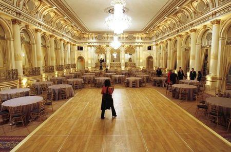 "A journalist walks across the dance floor in the ""Grand Ballroom"" of ""The Plaza"" hotel as it re-opens in New York"