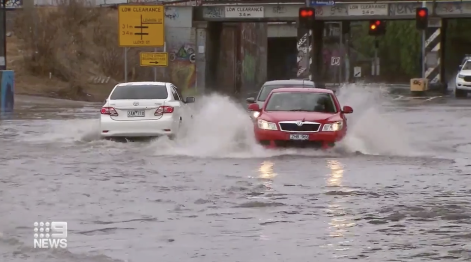 Cars in West Melbourne drive through wet streets.