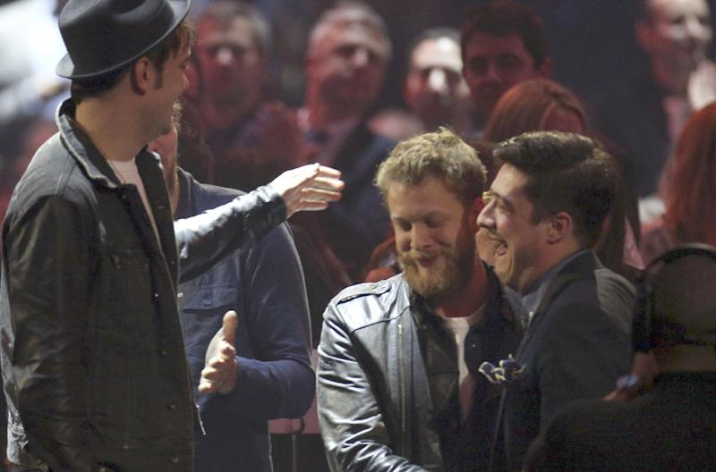 Marcus Mumford, right,  Ted Dwayne, 2nd right, and  Ben Lovett, of British band Mumford and Son react upon being announced winners of the Best British Group award during the BRIT Awards 2013 at the o2 Arena in London on Wednesday, Feb. 20, 2013. (Photo by Joel Ryan/Invision/AP)