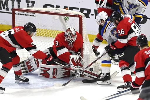 Ottawa Senators goaltender Anders Nilsson (31), defenseman Cody Ceci (5) and defenseman Christian Wolanin (86) try to control the puck against St. Louis Blues left wing Alexander Steen (20) during first-period NHL hockey game action in Ottawa, Ontario, Thursday March 14, 2019. (Justin Tang/The Canadian Press via AP)