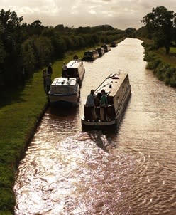Narrowboats travel along one of Britain's many waterways. VisitBritain/ Adrian Houston