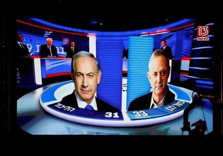 The results of the exit polls are shown on a screen at Benny Gantz's Blue and White party headquarters, following Israel's parliamentary election, in Tel Aviv
