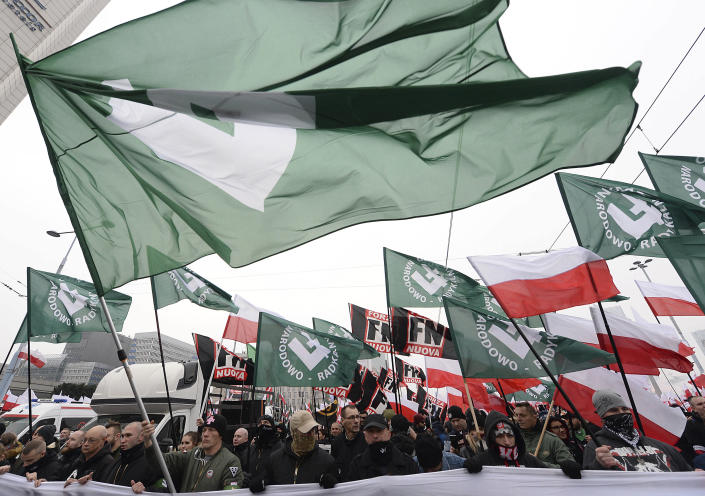 Members of radical right-wing groups wave flags during a march by tens of thousands of people and hosted by President Andrzej Duda that marked 100 years since Poland regained independence in Warsaw, Poland, Sunday, Nov. 11, 2018.(AP Photo/Czarek Sokolowski)
