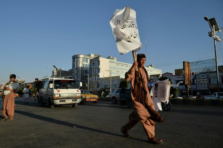 A boy selling Taliban flags looks for customers while walking along a road in Herat (AFP/Hoshang Hashimi)