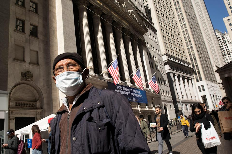 A man wears a mask as he passes the New York Stock Exchange, Monday, March 9, 2020. The dizzying action in financial markets escalated Monday as stocks moved closer to a bear market and oil prices fell the most since 2008.