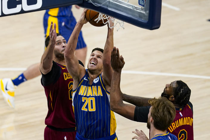 Indiana Pacers forward Doug McDermott (20) shoots between Cleveland Cavaliers forwards Larry Nance Jr. (22) and Andre Drummond during the first half of an NBA basketball game in Indianapolis, Thursday, Dec. 31, 2020. (AP Photo/Michael Conroy)