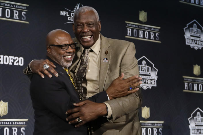 FILE - Hall of Fame Class of 2020 Donnie Shell, left, hugs Harold Carmichael at the NFL Honors football award show in Miami, in this Saturday, Feb. 1, 2020, file photo. Built more like an NBA player at 6-foot-8, Harold Carmichael turned to football because he couldn't perform basketball's most basic skill. Carmichael couldn't dribble. It worked out for the best. Carmichael used his size to outjump and overpower defenders, catching more passes for more yards and touchdowns than any player in the history of the Philadelphia Eagles. The gentle giant then waited patiently for three decades before he was elected to the Pro Football Hall of Fame as part of last year's special centennial class. (AP Photo/Mark Humphrey, File)