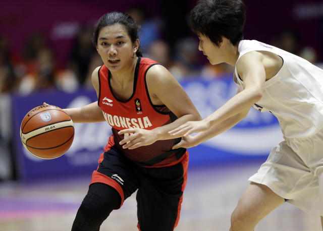 Indonesia's Christine Tjundawan, left, dribbles the ball past combined Korea's Kim Hye Yon during their women's basketball match at the 18th Asian Games in Jakarta, Indonesia, Wednesday, Aug. 15, 2018. (AP Photo/Tatan Syuflana)