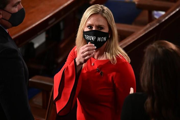 """FILE - In this Sunday, Jan. 3, 2021, file photo, Rep. Marjorie Taylor Greene, R-Ga., wears a """"Trump Won"""" face mask as she arrives on the floor of the House to take her oath of office on opening day of the 117th Congress at the U.S. Capitol in Washington. President Joe Biden's inauguration has sown a mixture of anger, confusion and disappointment among believers in the baseless QAnon conspiracy theory. Greene, who has expressed support for the conspiracy theories, called for Biden's impeachment across her Twitter, Facebook and Telegram accounts as the new president was sworn in, Wednesday, Jan. 20. (Erin Scott/Pool Photo via AP, File)"""