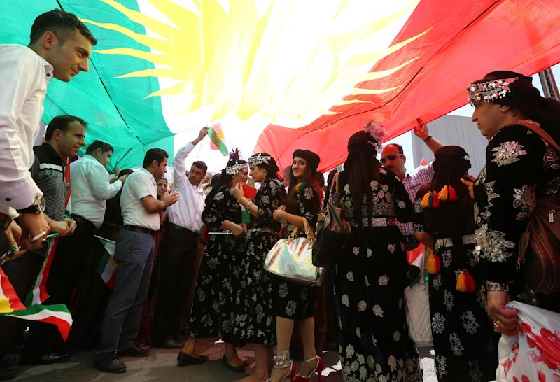 Iraqi Kurdish protesters deploy a giant flag of their autonomous Kurdistan region during a demonstration to claim for its independence on July 3, 2014 outside the Kurdistan parliament building in Arbil, in northern Iraq (AFP Photo/Safin Hamed)