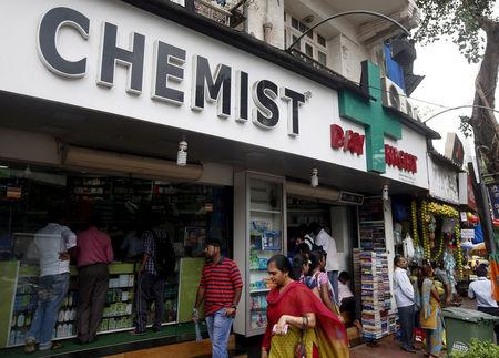 FILE PHOTO: People walk past a chemist shop at a market in Mumbai, India, June 25, 2015. REUTERS/Shailesh Andrade/File Photo