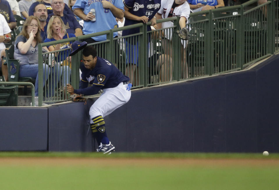 Milwaukee Brewers' Trent Grisham runs into the wall trying to catch a foul ball from Minnesota Twins' Jorge Polanco during the first inning of a baseball game Wednesday, Aug. 14, 2019, in Milwaukee. (AP Photo/Jeffrey Phelps)