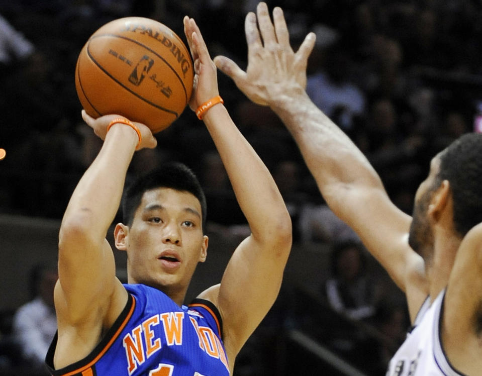 FILE - In this March 7, 2012 file photo, New York Knicks' Jeremy Lin, left, shoots over San Antonio Spurs' Tim Duncan during the first half of an NBA basketball game, in San Antonio. This would have been such an easy decision in February. Lin was the biggest thing in basketball, and no way the Knicks would have let him go elsewhere. Now, knowing his price and with no assurance he'll play as he did when Linsanity reigned, the Knicks may allow Lin to leave for Houston.  (AP Photo/Darren Abate, File)