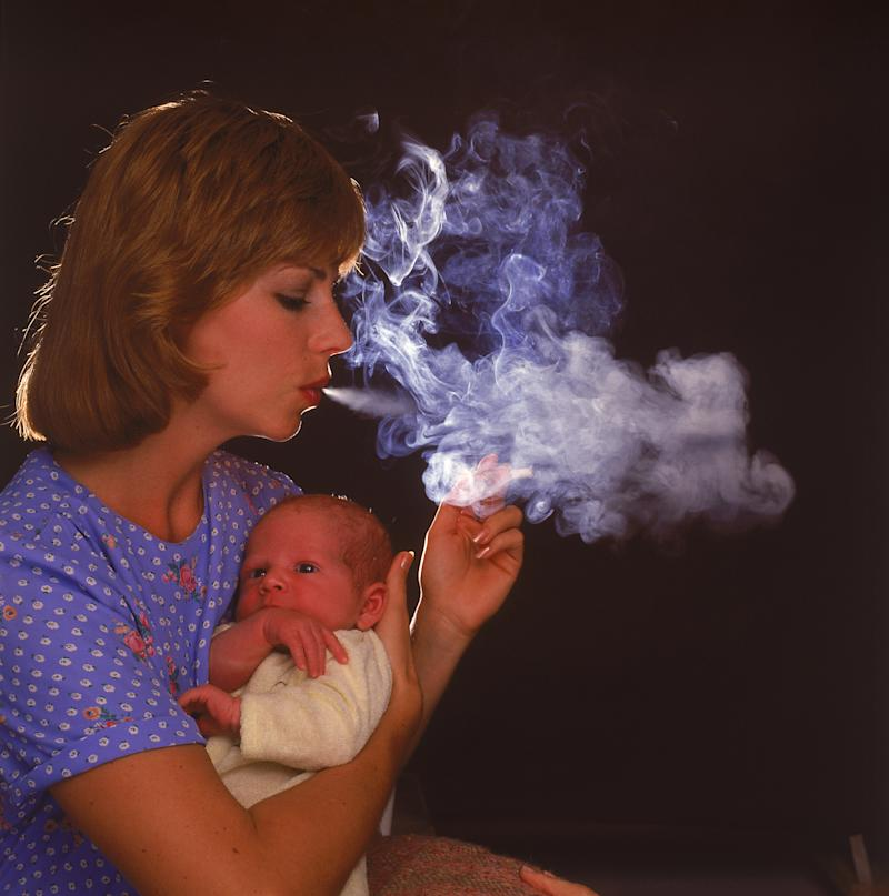 Smoking mother holding infant