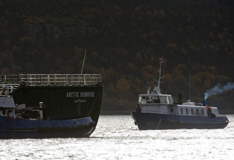 In this photo provided by Greenpeace International, a Russian Investigation Committee, right, approaches the Greenpeace International ship, Arctic Sunrise for an inspection, in a closed part of Murmansk port, Russia, Saturday, Sept. 28, 2013. Greenpeace said on Friday it will appeal the Russian court rulings that sent its activists to jail for a protest at an offshore drilling platform in the Arctic. (AP Photo/Greenpeace International, Dmitri Sharomov)