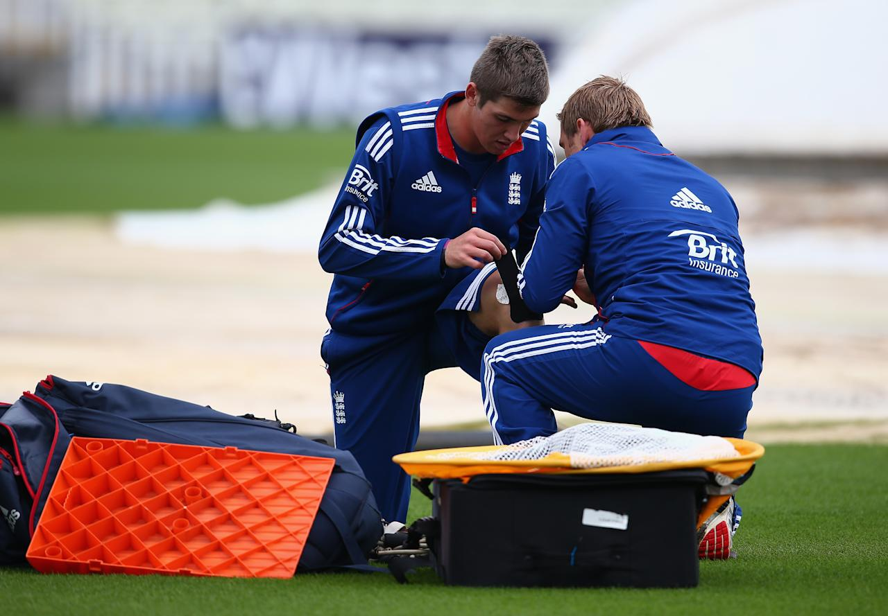 BIRMINGHAM, ENGLAND - SEPTEMBER 10:  Jamie Overton of England receives medical attention during a net session ahead of the third NatWest One Day International Series match between England and Australia at Edgbaston on September 10, 2013 in Birmingham, England.  (Photo by Clive Mason/Getty Images)