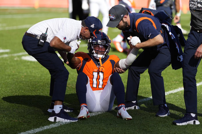 Denver Broncos wide receiver Diontae Spencer (11) is helped off the field after taking a hit against the Baltimore Ravens during the first half of an NFL football game, Sunday, Oct. 3, 2021, in Denver. (AP Photo/Jack Dempsey)